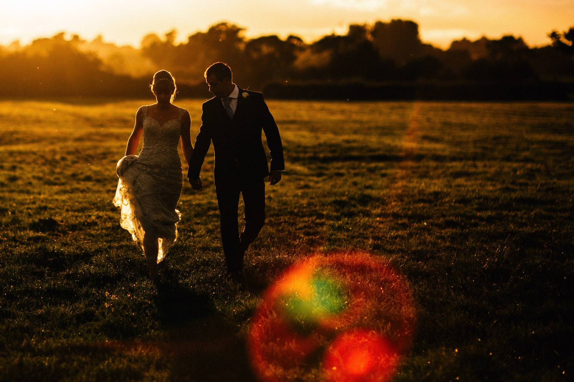 Best wedding photography 2016 - walking through a field at sunset