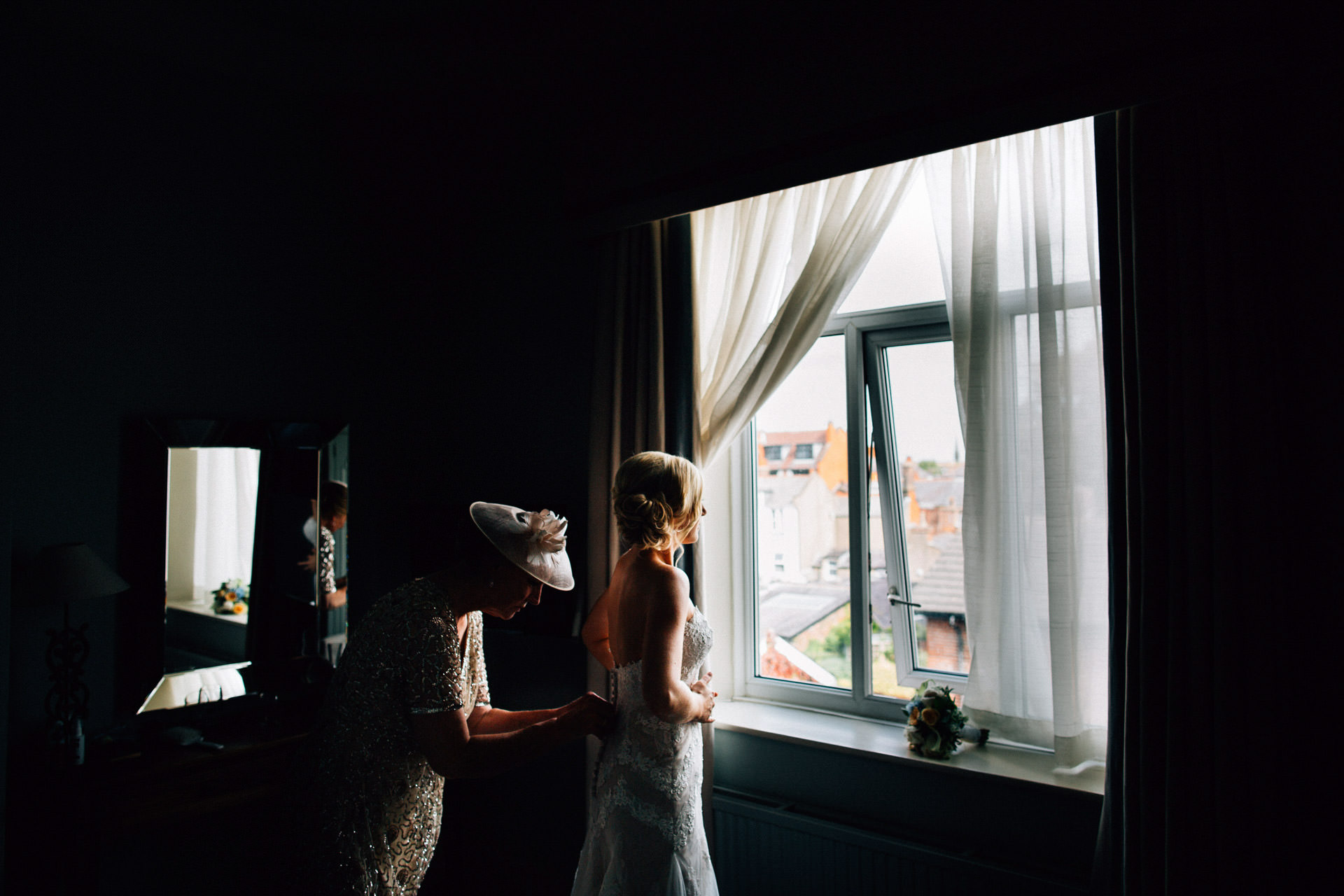 Best wedding photography 2016 - bride having her dress done up in window