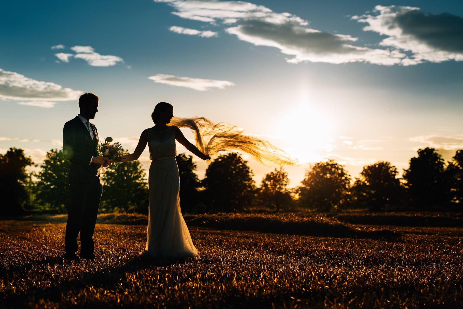 Best wedding photography 2016 - bride and groom walking through a field at sunset