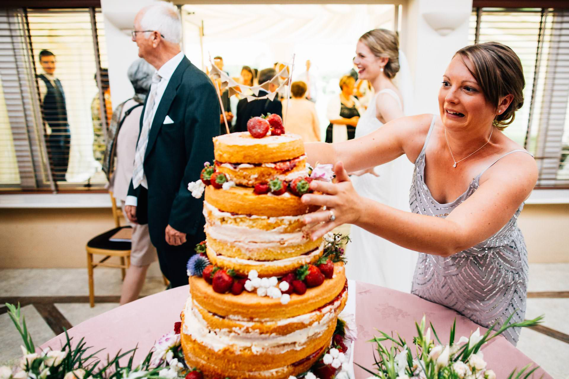 Best wedding photography 2016 - bridesmaid stopping the cake from falling over
