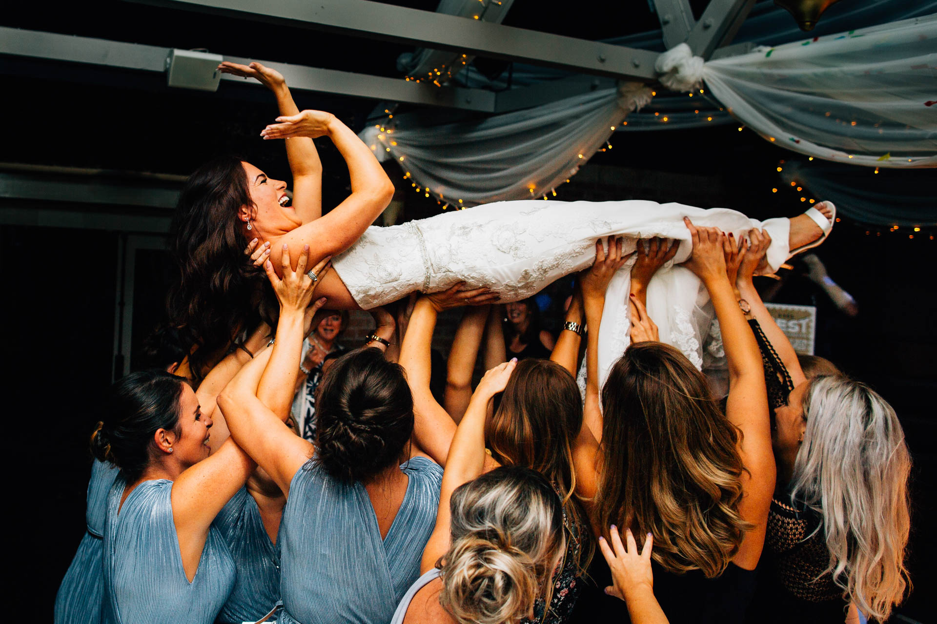 Best gear for professional wedding photography - bride being lifted up at evening reception