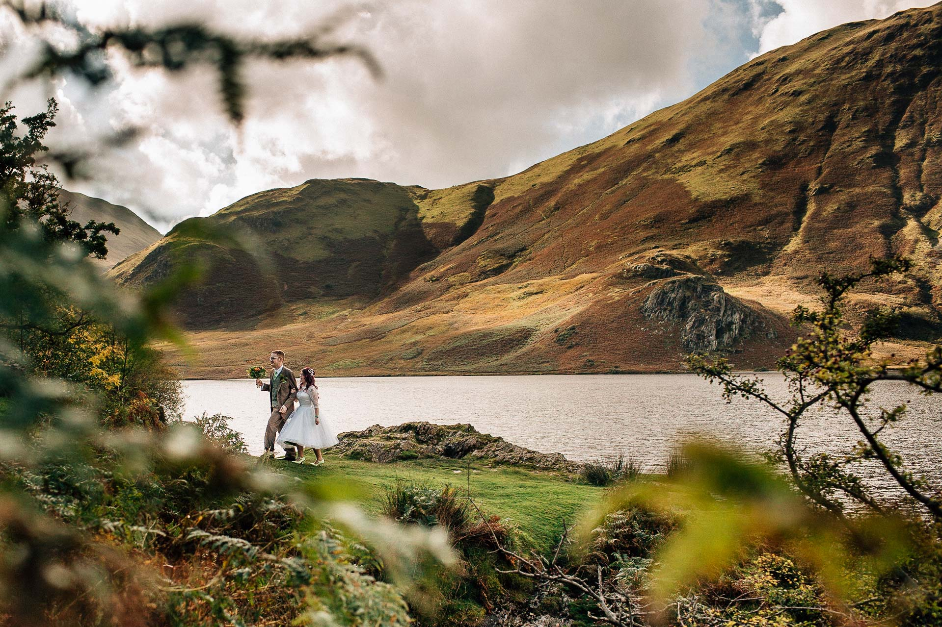 New House Farm Wedding Photography - N&P - bride and groom walking along lakeland path in cumbria