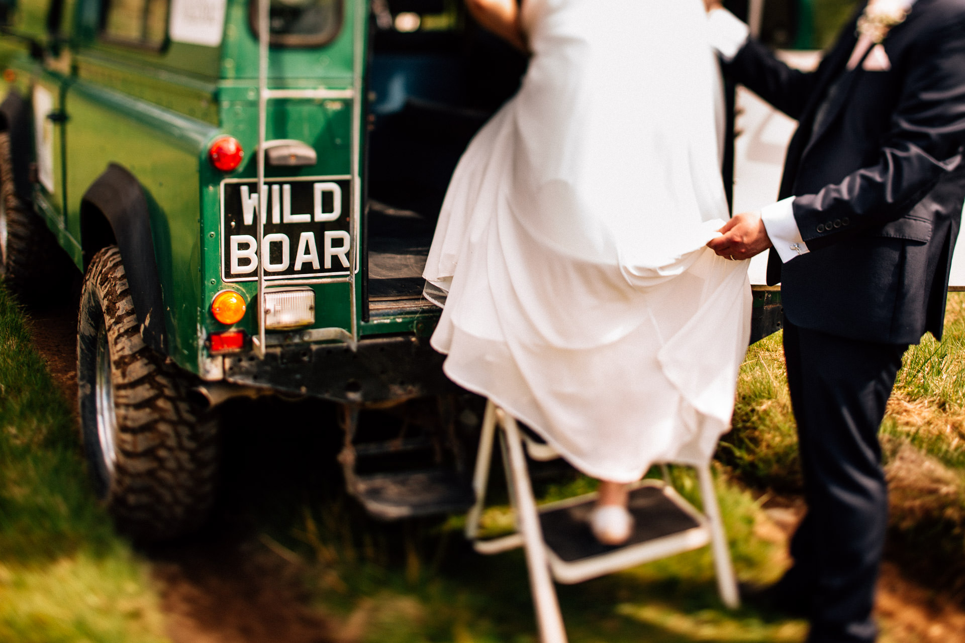 The Wild Boar Wedding Photography - EM - bride climbing into the back of a defender