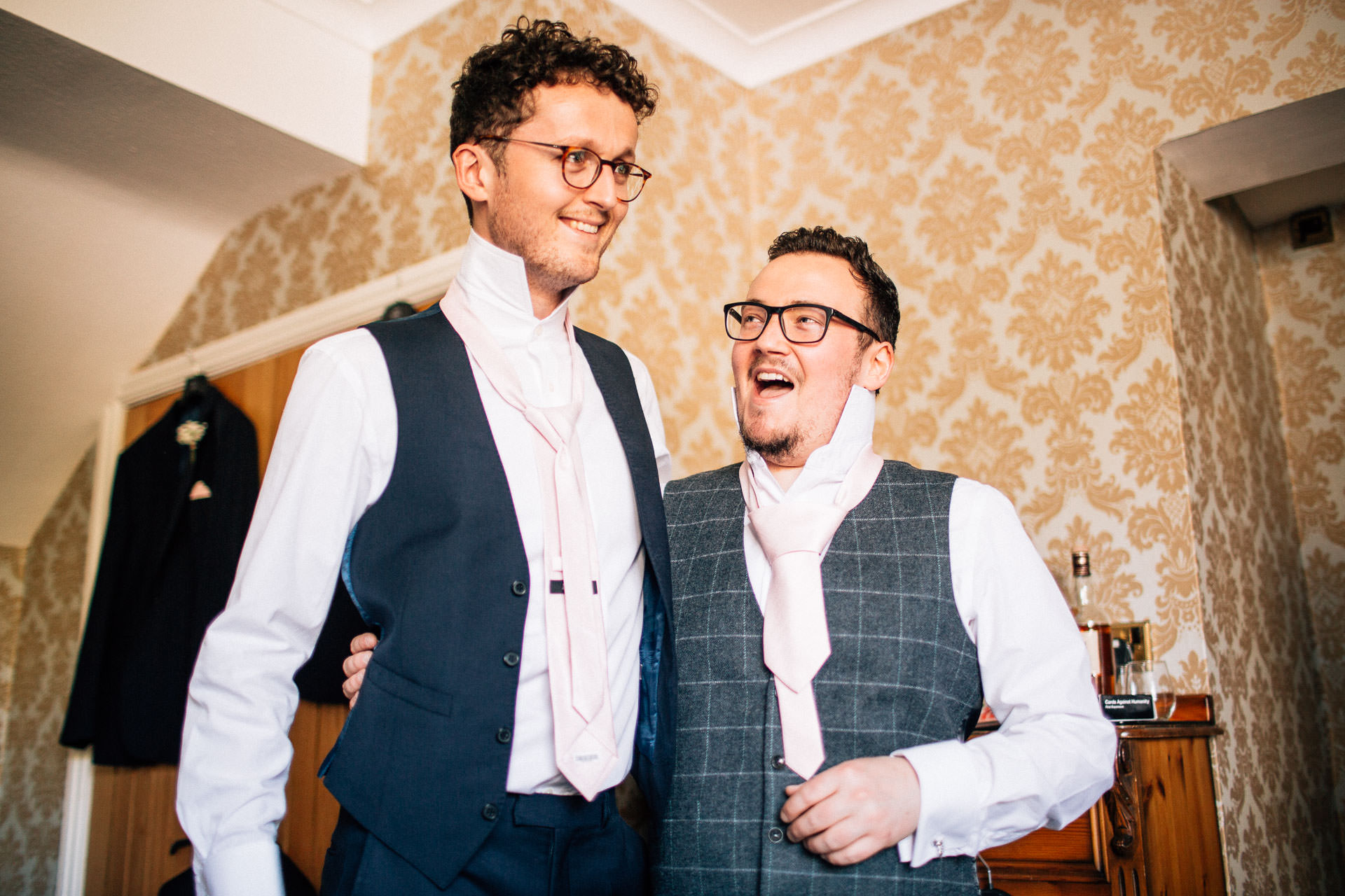The Wild Boar Wedding Photography - EM - groom laughing at terrible ties