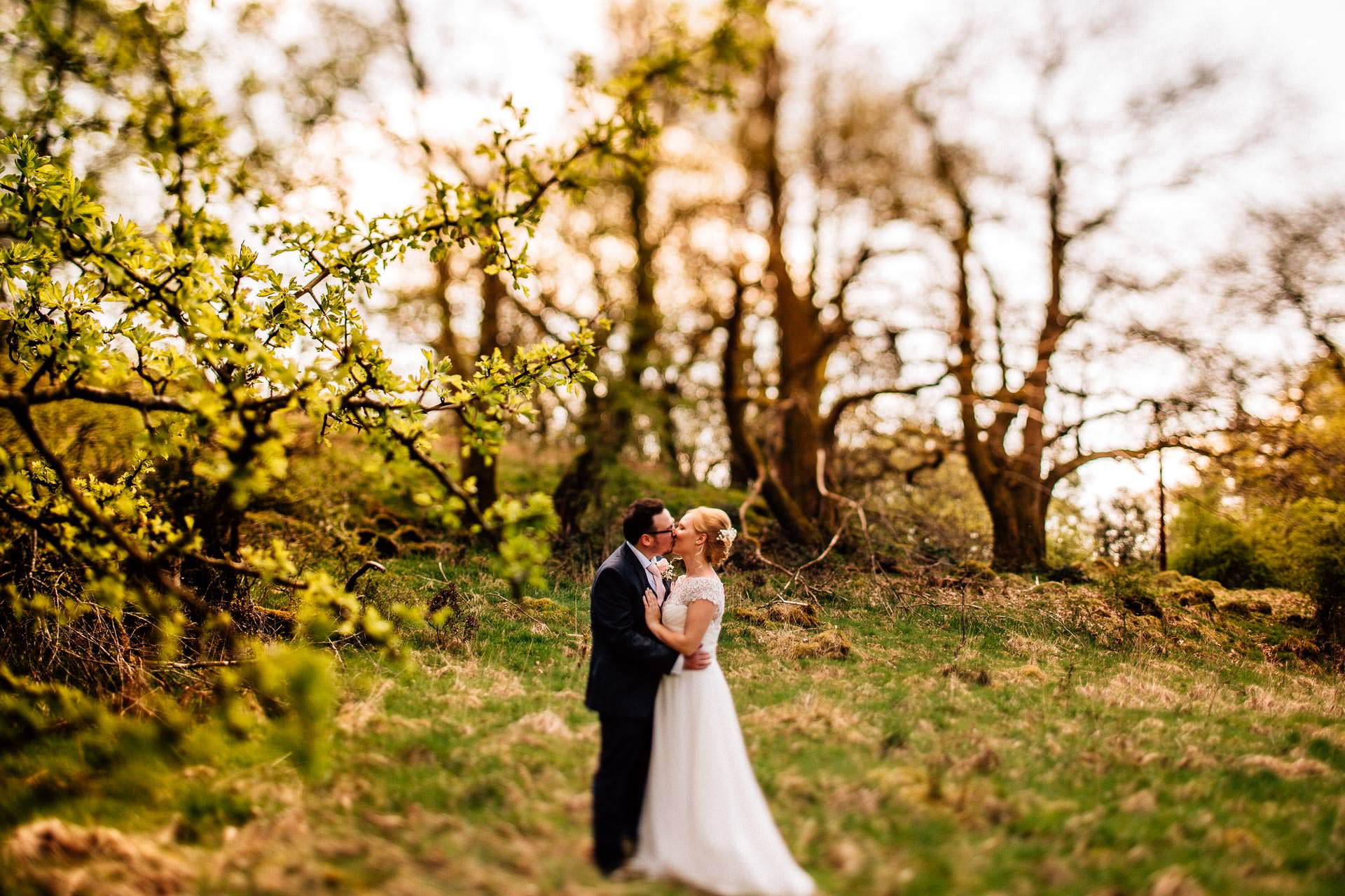The Wild Boar Wedding Photography - EM - couple kissing in the trees