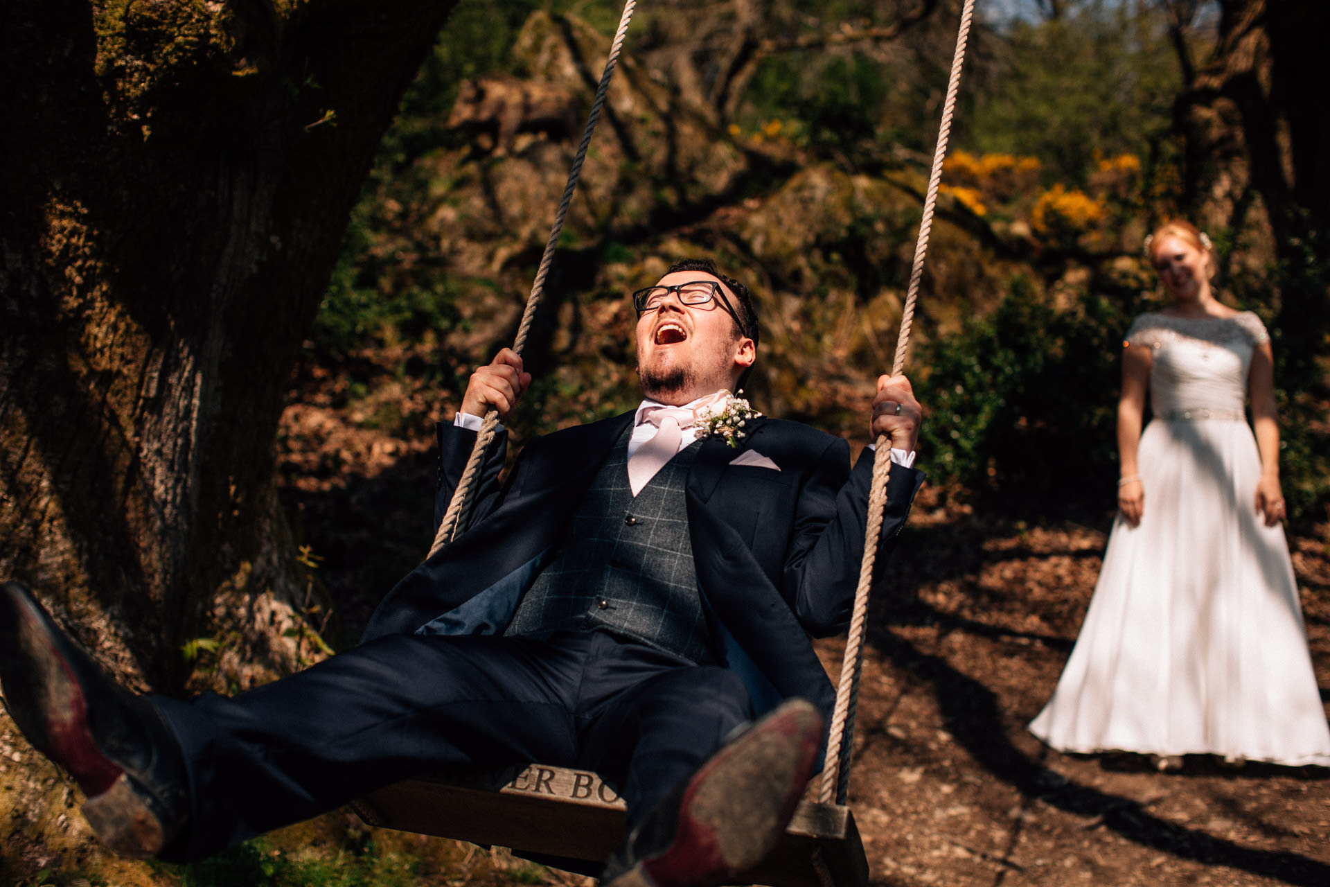 The Wild Boar Wedding Photography - EM - groom being pushed on swing
