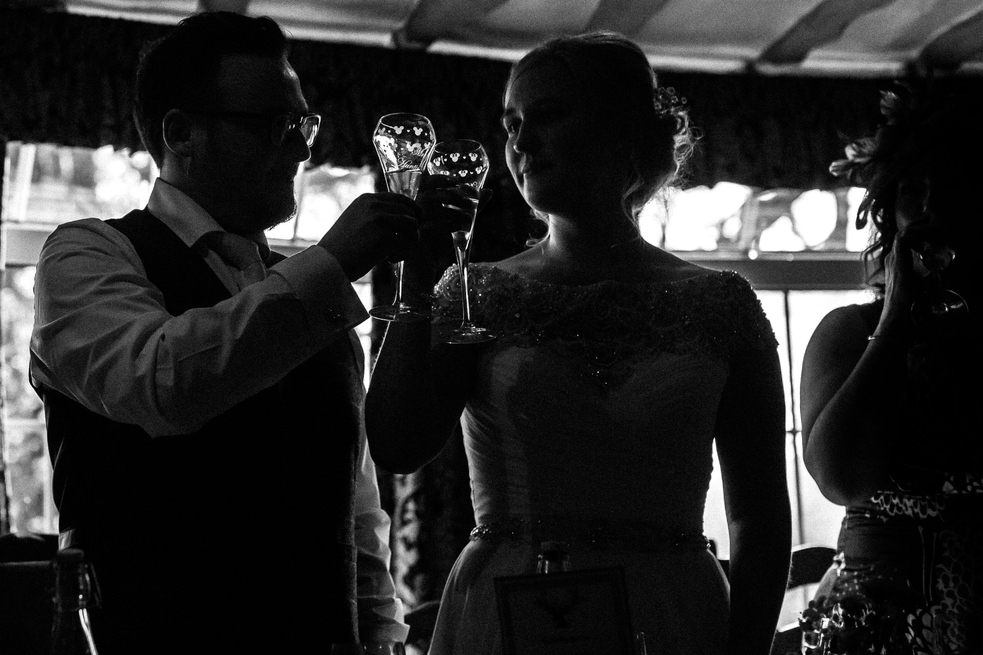The Wild Boar Wedding Photography - EM - silhouette of couple cheers after speech