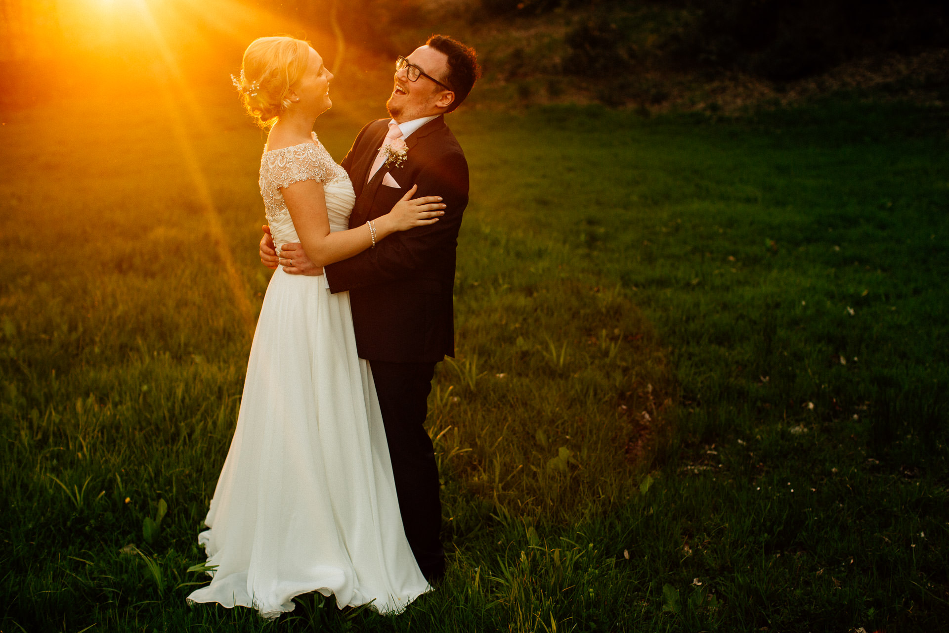 The Wild Boar Wedding Photography - EM - couple laughing together in sunset light